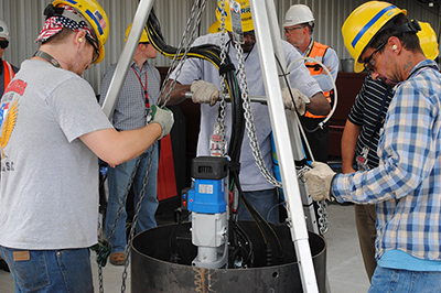 Workers test a modified cutting tool in a mock demonstration before using it to modify storage positions for waste canisters inside the Glass Waste Storage Building 1